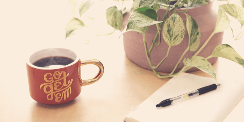 cup of coffee and a notebook for personal development ideas